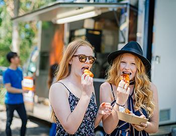 Two girls eating from a food truck