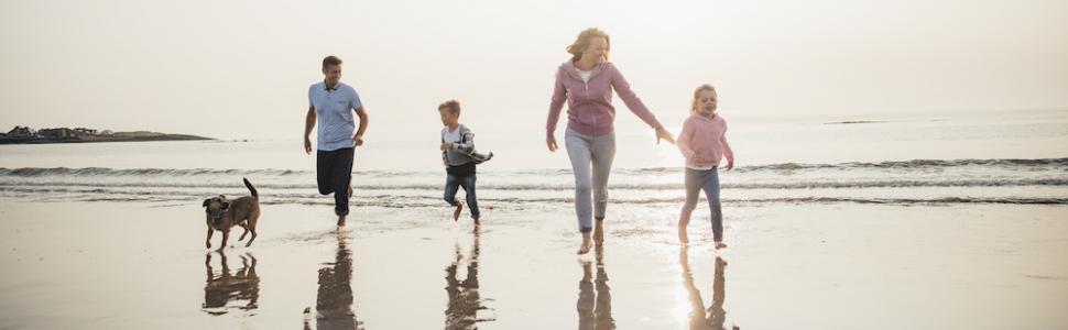 family on beach with dog